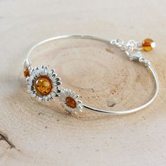 Triple sterling silver sunflowers bangle set with honey Baltic amber. The wire bangle includes an extender increasing the bangle to inches Amber Bracelet, Amber Jewelry, Rose Gold Jewelry, Crystal Jewelry, Sunflower Jewelry, Blue Topaz Necklace, Silver Ring Designs, Jewelry Auctions, Thing 1