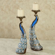 "Feathered Splendor Candleholders| Blue Set of Two Peacock Candleholders: Illuminate your home with the Feathered Splendor of this peacock candleholder set. Made of resin, these candleholders are accented with silver and bronze swirls and styled like regal peacocks. Clear acrylic gems accent the birds' feathers, along with brilliant blue touches. Their head crests fan out to hold the included 3""dia.x3""H ivory pillar candles. Small candleholder is 6.5""Wx4""Dx14""H; large is 7""Wx4""Dx16""H. • Set…"