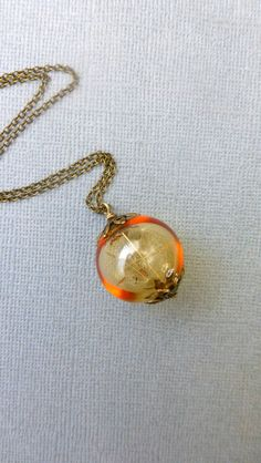 Dandelion seeds necklace  Amber glass orb by FlowerGiftByNature. I want most of their necklaces! So pretty.