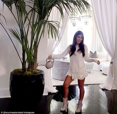 Doping the chores: A happy-looking Kourtney Kardashian shared a photo of herself watering sister Khloe's house plants on Monday while wearing a white mini dress and heeled boots