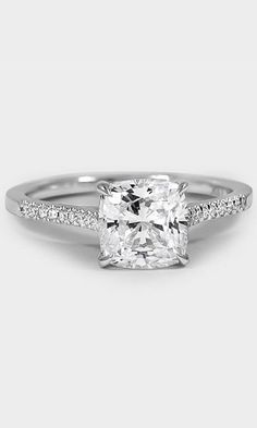 In this classically beautiful engagement ring scalloped pavé diamonds embellish the top half of the band.