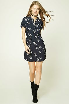 A woven mini dress featuring an allover floral print, a split collar, short button-tab sleeves, a round vented hem, and a self-tie waist.