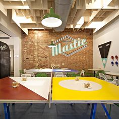 The design is focused around ping pong tables that retain their functionality as sports equipment (paddles are available on the walls) while doubling as dining tables. They contribute to a colourful, fun ambience aided by some great graphics...