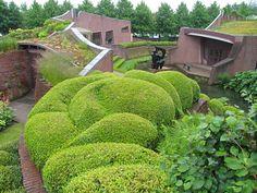 Organisch en Geometrisch omarmen elkaar bijna letterlijk in deze foto. Ook wordt er bewezen dat geometrisch niet altijd vierkant hoeft te zijn. Daarbij wordt bij de gebouwen geprobeerd om het organische naar buiten te laten komen door de golvende lijnen en groene daken.