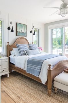 lake house bedding - crisp blue and white bedding with warm wood floors and jute rugs lend this lake house bedroom a coastal vibe.
