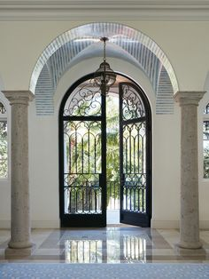 Grand arched double front door with delicate steel work - Kemble Interiors