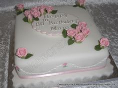 Traditional style square celebration cake with pink sugar roses and simple sugar plaque with a happy birthday mum message