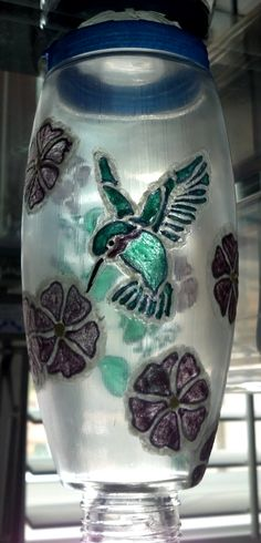 BOTTLE: Painted hummingbird feeder. (That is painter's tape at the top.) All the painted items are outlined in Glow-in-the-Dark paint, so at night... ;-)
