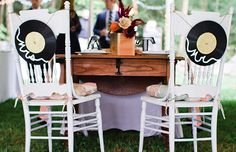 Sweetheart table with wedding chair signs that look like old vinyl records