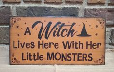 "Prim Style Halloween Witch Sign ""A Witch Lives Here with Her Little Monsters"" Handpainted. $24.99, via Etsy."