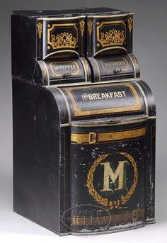 antiques price guide, antiques priceguide, country store, Ohio, Tole decorated spice bin by Mannen & Esterly of Cleveland, Ohio. Late 19th century spice bin in three sections with black with gold stencil decoration, three labeled bins with cylinder roll compartments marked WH PEPPER, MUSTARD SEED, and ENG BREAKFAST. The front decorated with a stenciled M within a wreath centered by stenciled belts.