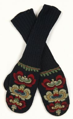 Mittens worn by a member of the Boeckmann family circa 1950. Mittens are of dark blue knitted wool and apppear to be forearm-length but may be intended to be cuffed. A mult-colored patterned knit overlay is sewn onto the top of each mitten.