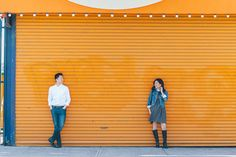 Couple pose against an orange gate during their engagement session at Coney Island. Captured by NYC wedding photographer Ben Lau.