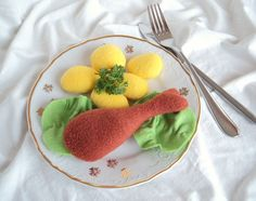 Kuřecí stehno s bramborem Jídlo do dětské kuchyňky- kuřecí stehno s bramborem a hlávkovým salátem. Velikost jídla je úměrná dezertnímu talířku. Stehno a brambory jsou ušity z fleece, salát z filcu. Plněno polyesterovým kuličkovým rounem vhodným pro alergiky. Praní do 40 °C.