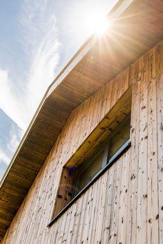Die Fassadengestaltung des Einfamilienhauses zeichnet sich durch die Ausrichtung der Fenster aus, welche an die Ausblicke auf die umliegende Berglandschaft angepasst ist. Das Haus spiegelt dadurch eine Transparenz wieder, was der Idee eines offenen Lebensstils und einem gefühlvollen Umgang mit der Natur nahekommt. Im Herzen des Hauses werden alle Stockwerke durch eine offene Deckenkonstruktion miteinander verbunden, was im Innenraum ein Atrium entstehen lässt. Atrium, Stairs, Home Decor, Room Interior, Windows, Mountain Landscape, Detached House, Environment, Interior Designing