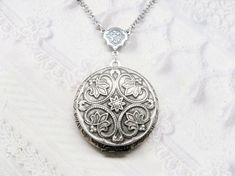 A beautifully ornate medallion is mounted onto a silver plated locket that hangs from a vintage inspired rosary connector. This locket is available