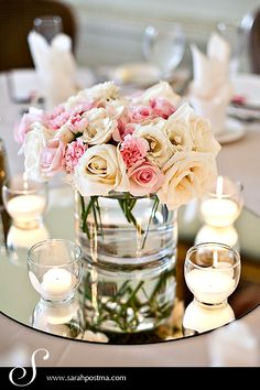mirror the teal vase in the middle with a full bouquet or red flowers, and then small tea light candles in frosted votives surrounding them.