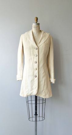 Antique 1910s cream mid-weight wool walking jacket with lovely detailed shoulders, cuffed and detailed sleeves, breast pocket, princess seaming for a close to the body fit, cubtle cutaway shape and very sweet floral silk lining.  --- M E A S U R E M E N T S ---  fits like: xs shoulder: 15 bust: 32-34 waist: 30 hip: 38 sleeve: 23.5 length: 33 brand/maker: n/a condition: this coat is in great wearable condition but does show its age with some moth holes, general wear to the edges and ...