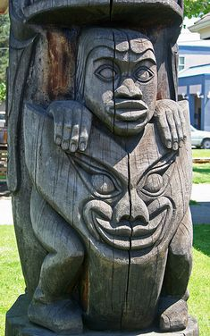 Close-up of the carving of an old weathered Northwest Coast totem pole.