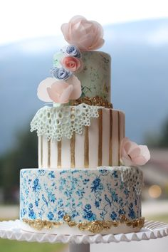 Romantic feeling wedding cake with blue, blush and gold details. Lovely vintage feeling doily and fondant flower cake topper.
