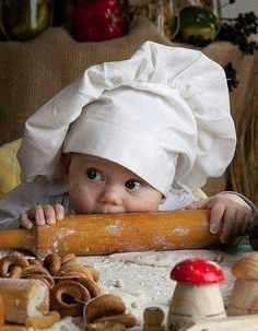 Baby in chef hat with rolling pin, bake