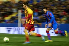 Lionel Messi (L) of Barcelona runs with the ball beside Nikolaos Karampelas of Levante during the Copa del Rey Quarter Final First Leg match between Levante UD and FC Barcelona at Ciutat de Valencia on January 22, 2014 in Valencia, Spain.