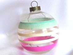 This vintage, unsilvered Christmas ornament was made in the USA. The large glass holiday ornament has narrow white bands in the middle, bounded