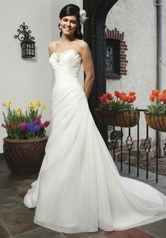 An asymmetric organza draped A-line gown with a beaded sweetheart neckline. This style has a lace up back and a chapel length train.