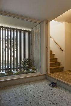 大きな窓を通して坪庭を眺められる玄関