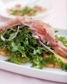 Yummy salad with cantaloupe, arugula (rocket), and prosciutto