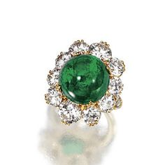 CABOCHON EMERALD AND DIAMOND RING, VAN CLEEF & ARPELS, CIRCA 1965.  Set with a highly domed cabochon emerald encircled by 10 round diamonds weighing approximately 5.40 carats, the shoulders accented with 12 small round diamonds, mounted in 18 karat gold, size 6, obscured signature.