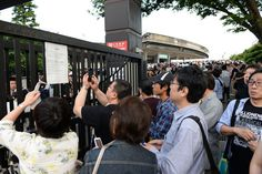 Fans take a photograph of the sign announcing the cancellation of the Paul McCartney show to be held at the National Stadium on May 17 in Tokyo, Japan.