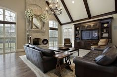 Spacious family room in luxury home with cathedral ceiling, exposed wood beams, dark leather furniture, large rug and entertainment cabinet