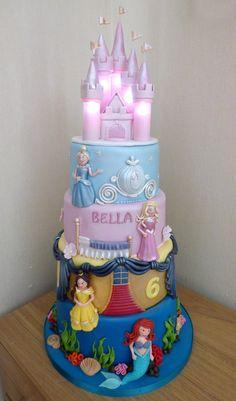 4 tier disney princesses birthday cake with an illuminated castle