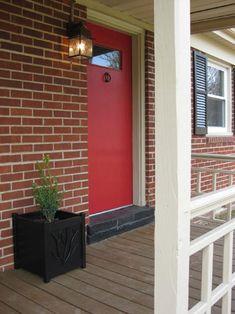 Brick house, black shutters, white trim, RED door