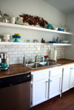 white cabinets, butcher block counter tops, and open shelves (and check out the turquoise knobs)