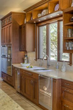 Frame your kitchen sink and make it a focal point, using symmetry for balance. The cabinet above with the upper cabinets frame the window, add an onlay to the false drawer below the sink, arrange appliances equally on each side with fluted pull out cabinets on the end to finish it off.