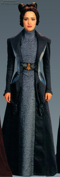 This high-necked dress and floor length jacket with embroidered waist detail is worn by Padme Amidala's handmaiden Dorme in Star Wars Episode II.