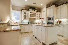Lovely white kitchen // Granite countertops, island, natural light, stainless appliances, and lots of varied cabinetry