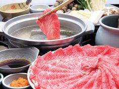 """Shabu-shabu, meaning """"swish swish"""", is prepared by submerging thinly sliced beef and vegetables in a pot of boiling water and swishing it back and forth until cooked. Cooked meat and vegetables are usually dipped in various sauces before eating, and served with a bowl of steamed white rice."""