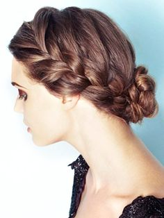 Create a side part. From the larger side of your part, take a 2-in section of hair from where your part begins. French braid your hair along the side of your head until the braid reaches the nape of your neck. Repeat with a similar braid on the other side of your head. At the nape of your neck, braid the hair from both sides into one loose braid. Wrap the braid into a bun at the nape of your neck, and secure with an elastic and bobby pins. Gently loosen the braids on the sides.