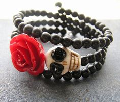 3 loops of silver plated memory wire. Black plastic beads, 24mm red resin rose Skull is 18mm howlite in cream. Wraps around to fit most size wrists.