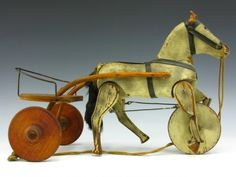 Late Victorian white wooden horse with fore wheel, articulate legs attached by wires. Wooden carriage with Trot-A-Way Prince decal to seat. Fully functional, horse even includes cord bridle. Brown oilcloth ears.