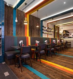 Mixing bright colors with wood floor paneling along the walls | Gourmet Burger Kitchen (Nottinghill, London)