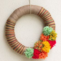 Pom-Pom Yarn Wreath For those holiday decorators who love to customize their creations, this DIY yarn wreath is for you. Simply wrap a straw wreath with complementary colors of yarn; the longer you wrap with a color, the thicker the stripe. Finish with a cluster of yarn pom-poms and your front door will be this season's star.