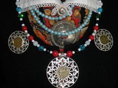 Traditional finery of West Estonia: a necklace so called paater: beads with 3 kodarraha (spoked coin pendants), and  kuhiksõlg (conical brooch).