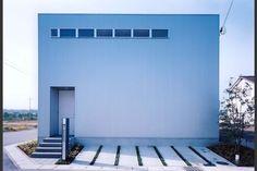 北東角地の北側からのシンプルな外観。外壁はシルバーのガルバリウム鋼板スパンドレル、中庭部分のみ漆喰仕上げとして内と外の表情を変えている。