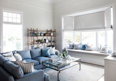 White and blue living room features beadboard walls accented with trim moldings framing a by window dressed in gray roman shades filled with a built-in window seat adorned with gray and blue pillows. Beach Interior Design, Coastal Living Rooms, Transitional Living Rooms, Window Design, Bay Window, Window Blinds, Room Window, Living Room Inspiration, Contemporary Furniture