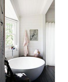 Modern bad in landelijke badkamer met houten vloer en wanden.