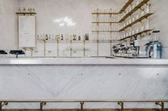 Royal Exchange Grind by Biasol: Design Studio. white marble bar front counter. white cafe interior with brass details